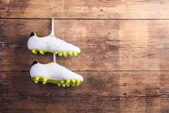 Football shoes on the floor. Pair of football shoes hang on a nail on a wooden fence background Royalty Free Stock Photo