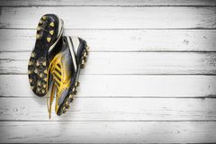 Football shoes hanging on wooden wall royalty free stock image