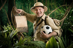 Football. Smiling explorer in the jungle holding a soccer ball leaning to a sign Royalty Free Stock Photography
