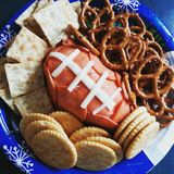A Superbowl treat. Football snacks of pepperoni, cheese ball, crackers and pretzels stock photo