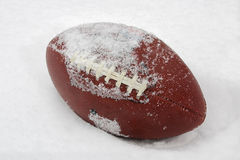 Football in the Snow. A football covered with snow and laying in the snow Stock Photos