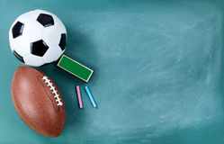 Football and soccer ball on cleaned chalkboard with eraser and chalk. American football and soccer ball on cleaned chalkboard with eraser and chalk stock photo