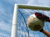 Football - soccer ball in goal. Goalkeeper,hands, gloves, football, sky, blue Royalty Free Stock Photo