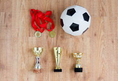 Football or soccer ball, golden cups and medals Royalty Free Stock Photo