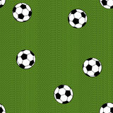 Football (soccer) ball on green field background. Seamless patte Royalty Free Stock Photos