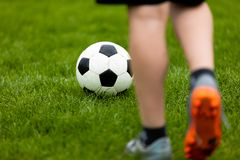 Football or soccer ball at the kickoff of a game. Soccer free kick at a grass pitch. Young soccer player with traditional football ball Stock Image