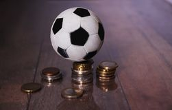 A Football or soccer ball and a pile of money. Indicating the role finance play in sport Royalty Free Stock Image
