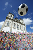 Football Soccer Ball Salvador Bahia Brazil. Football soccer ball in the air above wall of Brazilian wish ribbons at the Bonfim church in Salvador Bahia Brazil royalty free stock photography
