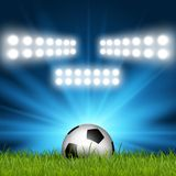 Football / soccer ball under spotlights. Nestled in grass Royalty Free Stock Photo