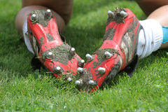 Football or soccer boots. Football boots with spikes on grass pitch Stock Photos
