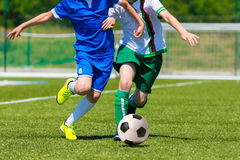Football soccer competition. Young boys playing football soccer game. Running players in blue and white uniforms Stock Image