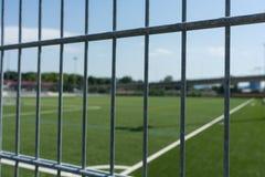 Football soccer field viewed through gate Stock Photos