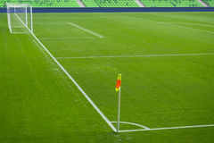 Football soccer field with white marks, green grass texture and corner flag. Royalty Free Stock Photo