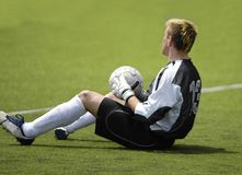 Football soccer goalkeeper. Goalkeeer sitting on the grass with the ball in his hands Stock Images