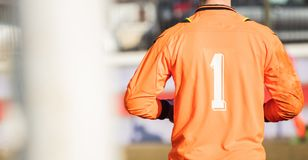 Soccer goalkeeper from behind view. Abstract background, close up, details, banner, space. Football Soccer goalkeeper with orange color uniform and number one Stock Photos