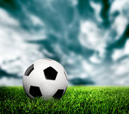 Football, soccer. A leather ball on grass, lawn. Dramatic sky, grunge style Stock Photo