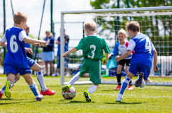 Football soccer match for children. Boys playing football game outdoor Stock Image