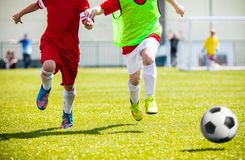 Football soccer match for children. Boys playing football game. On a school tournament. Dynamic, action picture of kids competition during playing football Royalty Free Stock Photo