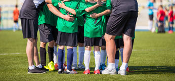 Football soccer match for children. Coach giving young soccer team instructions. Youth soccer team together before final game Royalty Free Stock Photo