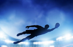 Football, soccer match. A goalkeeper jumping saving the ball from goal Stock Photos