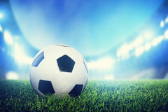 Football, soccer match. A leather ball on grass on the stadium. Football, soccer match. A leather ball on grass, lawn. Lights on the stadium at night Stock Photo