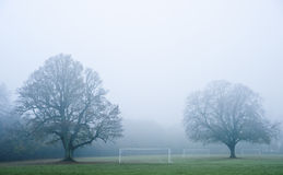 Football soccer pitch on foggy morning. Beautiful image of foggy misty forest in Autumn Fall ith football soccer pitches Royalty Free Stock Photos