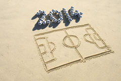 2014 Football Soccer Pitch Line Drawing in Sand. Simple line drawing of football pitch with soccer ball 2014 message in sand on Brazilian beach Stock Image