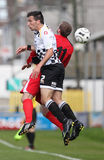 Football Soccer Player. Carlos Castan (white) of Neath FC competes for the ball against Osian Jones (red) of Bala Town during their Welsh Premier League match Royalty Free Stock Image