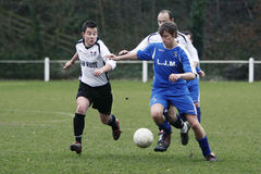 Football Soccer Player. Pontypridd Town (white) and Garw (blue) players fights for the ball during their Welsh Football League 2 match at Ynysangharad Park stock images