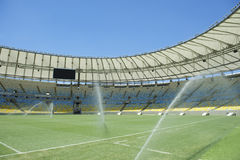 Football Soccer Stadium Sprinklers Spraying Grass. Pitch-level view of Maracana football soccer stadium with sprinklers Royalty Free Stock Image