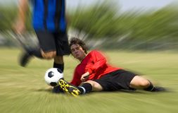Football - Soccer - Tackle!. Football - Soccer player making sliding tackle royalty free stock photography