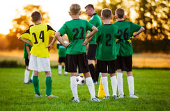 Football Soccer Training for Children. Soccer Team Training. On Pitch. Young Boys Standing in a Row. Youth Football Team with Coach on Training Session. Soccer Stock Photos
