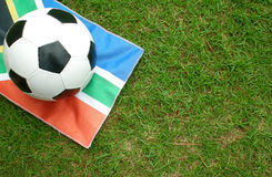 Football on South African flag. Closeup of football on South African flag with green grass background Stock Photo