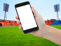 Football sport background. Football field with green grass and hands holding phone with blank screen Stock Image