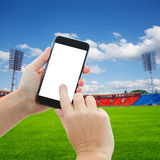 Football sport background. Football field with green grass and hands holding and pointing at phone with blank screen Royalty Free Stock Photography