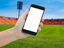 Football sport background. Football field with lamp post and green grass and hands holding and pointing at phone with blank screen Stock Photos