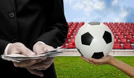 Football sport business concept. Ball in hand and cash in hand Royalty Free Stock Photos