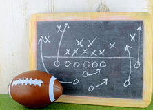 Football. Sports theme of toy football next to worn chalkboard with a play plan drawn out. Grass and wood background.Side lighting applied from left royalty free stock photography