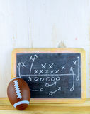 Football. Sports theme of toy football next to worn chalkboard with a play plan drawn out. Rustic wooden background. Vertical composition with copy space royalty free stock image