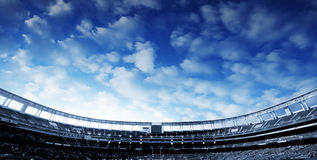 Football Stadium. Wide Horizontal photo of a american football stadium with blue clouds in the sky Royalty Free Stock Image