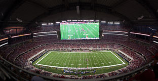 Football Stadium. Wide Angle Horizontal photo of a filled  american football stadium. Domed indoor stadium with large replay screen showing live game action Stock Images