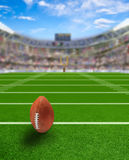 Football Stadium With Ball on Field and Copy Space. American football stadium full of fans in the stands with ball ready for kickoff or field goal on the field Stock Images
