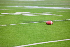Football on Stadium Field. A dirty football on a professional artificial turf football field near the 30 yard line Stock Photo