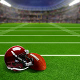 Football Stadium With Helmet and Ball and Copy Space. American football stadium full of fans in the stands with football helmet and ball on the field. Deliberate Stock Images
