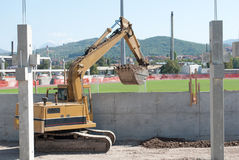 Football Stadium Reconstruction. Site with hydraulic excavator in action Royalty Free Stock Photography