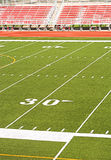 Football Stadium Red Bleachers. Football field viewed from high angle - red bleachers in background Stock Images