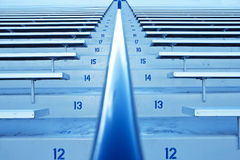 Football Stadium Seating. Stadium bleachers and seating, row after row of blue stadium benches stock photo