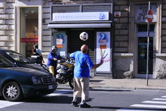 Football in the street. Rome, Italy - 21 September 2013. A man is bouncing a ball with his head in the middle of the street royalty free stock image