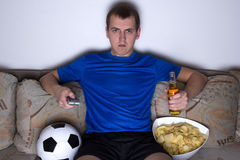Free Football Supporter In Uniform Sitting In Living Room And Watching Tv With Beer And Chips Stock Image - 38128081