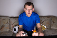 Football supporter in uniform watching tv Stock Photos